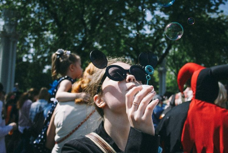 Teenage girl blowing bubbles against crowd