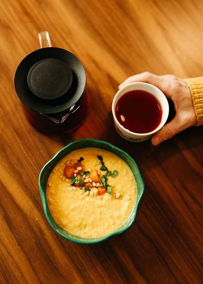 Yellow healthy pumpkin vegetarian porridge in a plate, a pot of tea and a mug on a wooden table