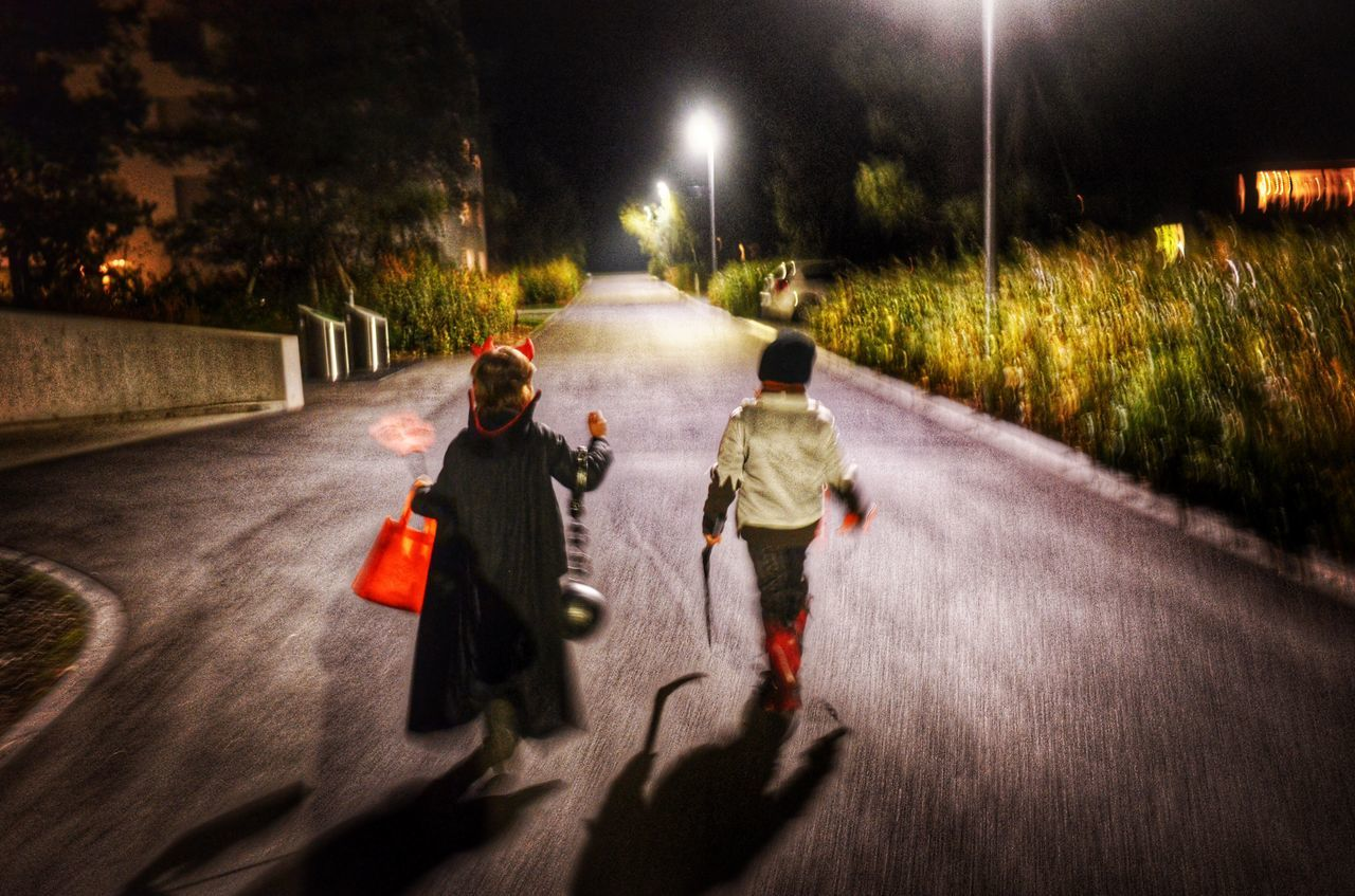night, illuminated, boys, two people, childhood, road, full length, walking, street, child, the way forward, street light, real people, outdoors, togetherness, transportation, tree, sky, people