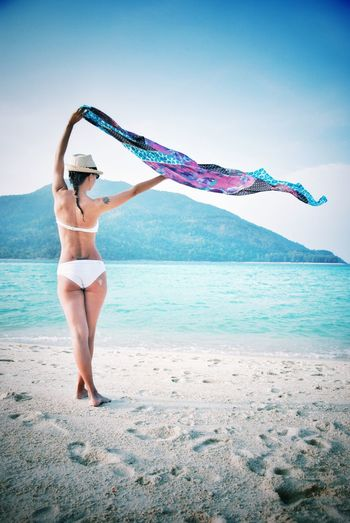 Rear view of woman standing while holding sarong aloft at beach against sky