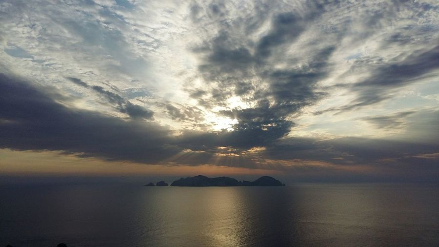 Palmarola island and sea against cloudy sky during sunset