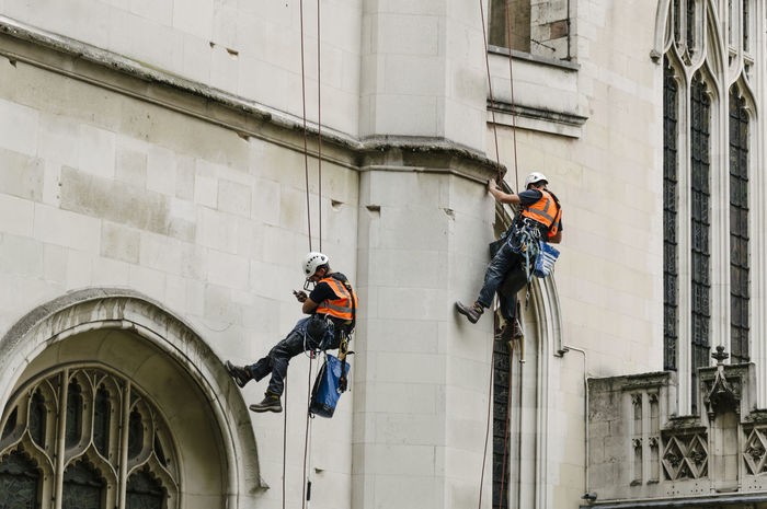 Two workers working on the facade of a church in maintenance work anchored with ropes with safety harnesses Anchored Cathedral Church Construction Hanged Harness Job London Maintenance Men Real People Real World Rehabilitation Ropes Safety Vertical Work Safety Worker
