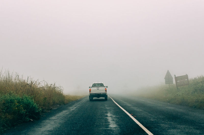 A white pick up truck drives through down a foggy highway at Blyde River Canyon Nature Reserve Car Cold Temperature Day Direction Fog Land Vehicle Mode Of Transportation Motion Motor Vehicle No People on the move Outdoors Road Road Trip Sign The Way Forward Transportation Travel Truck
