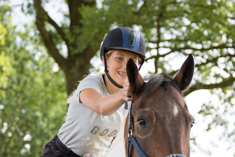 Happy teenager touching ear of horse
