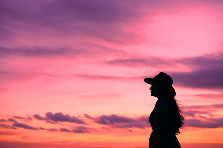 Side View Of Silhouette Woman Standing Against Orange Sky