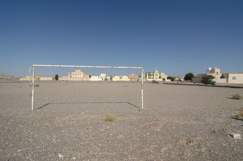 View of soccer field against clear blue sky