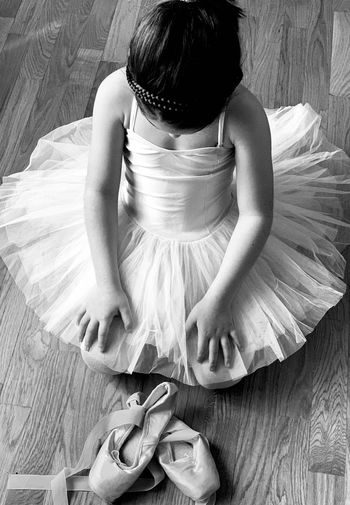 High angle view of girl with ballet shoes kneeling on floor
