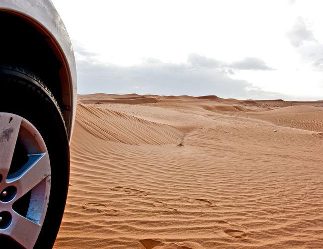 Close-up of car in desert against sky