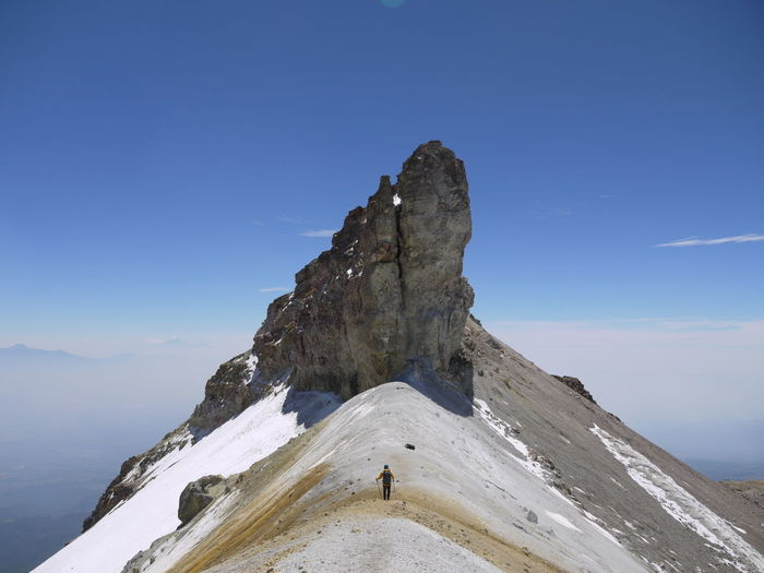 Man Hiking On Mountain Peak Against Sky
