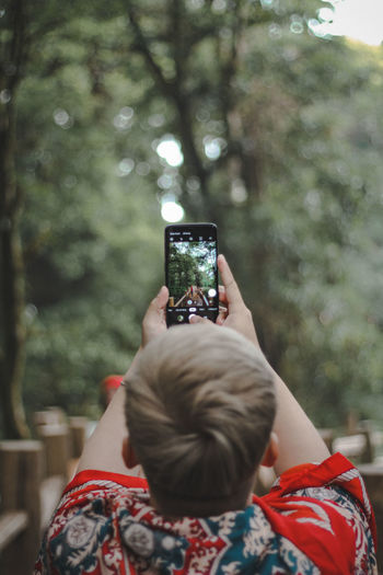 Rear view of man photographing from mobile phone at forest