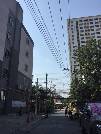 Building Exterior Built Structure Architecture City Street Car Transportation Road Sky Land Vehicle Outdoors Residential Building Day City Life Tree Electricity Pylon Red Light No People Traffic Signal Blue Sky Sky And Clouds Bangkok The City Light Architecture Clear Sky