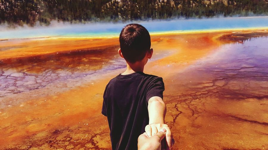 Cropped Hand Holding Boy By Geyser At Yellowstone National Park