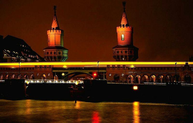 Illuminated Oberbaum Bridge Over River Spree Against Sky At Night