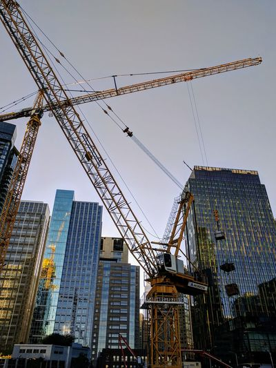 Cranes in city against sky