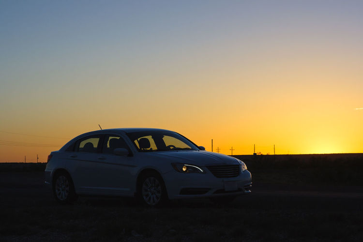 Car on road against clear sky during sunset