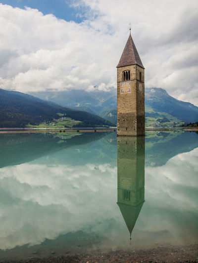 Cloud - Sky Water Built Structure Reflection Sky Architecture Building Exterior Tower Lake Religion Building Nature Mountain Spirituality Waterfront No People Belief Day Place Of Worship Mountain Range Outdoors Spire