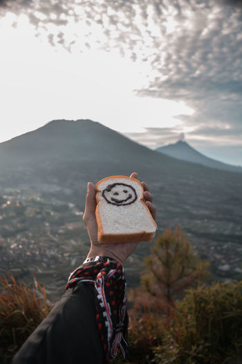 Cropped hand of holding bread against mountains