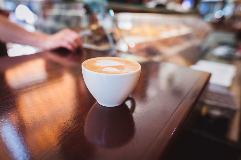 Cropped hand of man by coffee on table at store