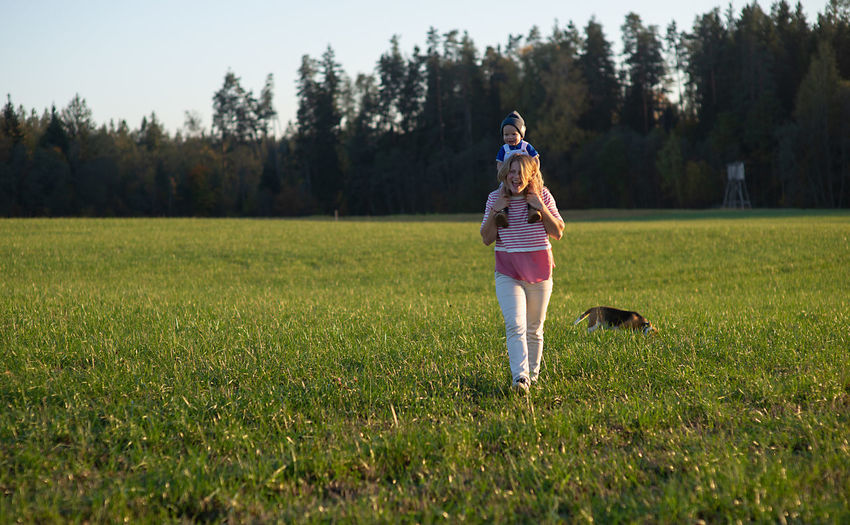 Happy mother carrying son on shoulders while walking on grassy field in park