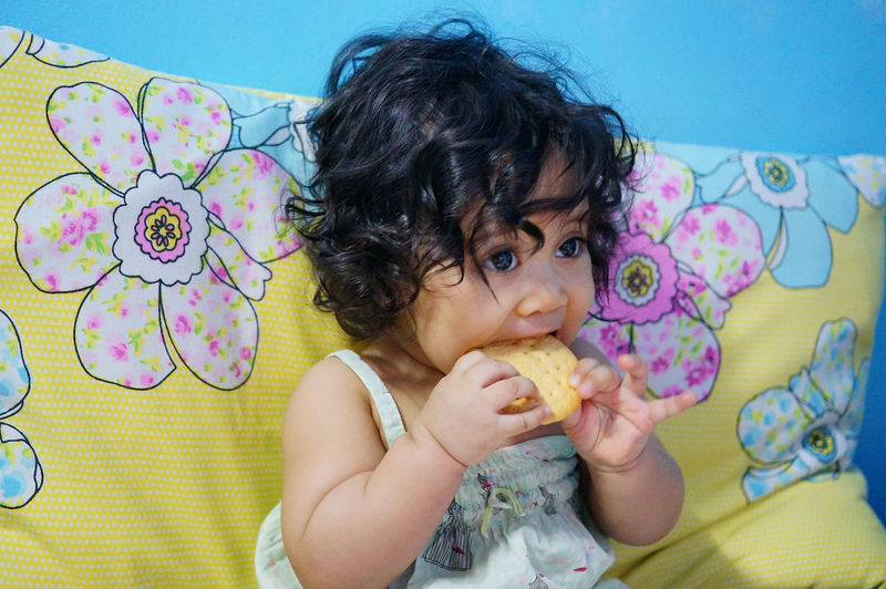 Close-up of cute baby girl eating biscuit while sitting on sofa