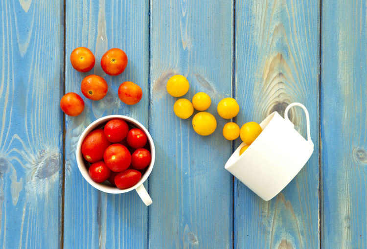 two white cups with red,yellow and orange tomatoes pouring them onto a blue wooden textured background Blue Cherry Tomatoes Day Freshness Fruit Healthy Eating No People Outdoors Red Small Tomatoes Tomatoes Wood - Material Wooden Texture