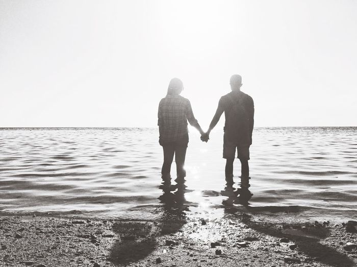 Rear View Of Friends Holding Hands While Standing In Sea At Beach