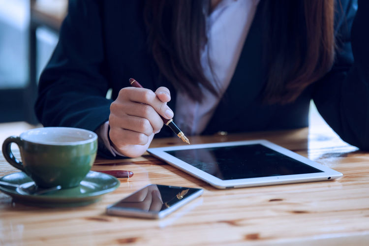 Midsection of businesswoman working on digital tablet at office desk
