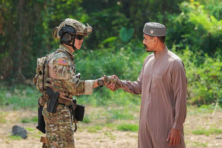 Side view of soldier shaking hand with man outdoors