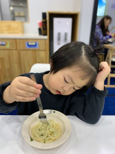 Close-up of girl eating noodles while sitting at home