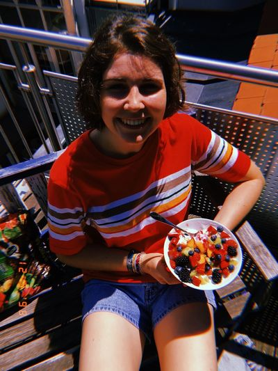 High angle view of smiling young woman holding fruits in plate during sunny day