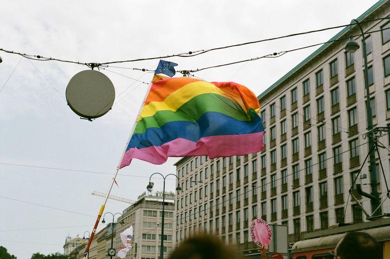 Rainbow flag waving in city against sky