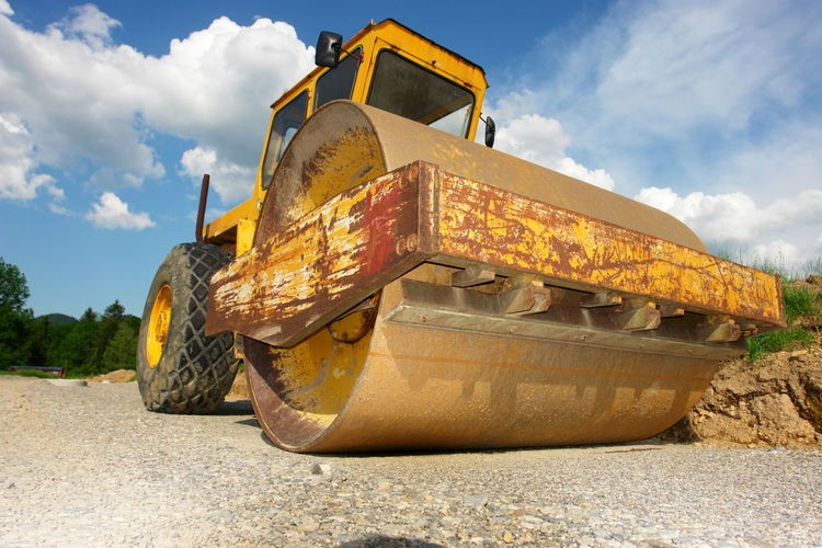 Low angle view of bulldozer on road against sky