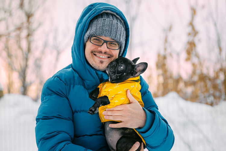 Looking At Camera Snow Covered Trees One Person One Man Only One Animal Domestic Animals Dog French Bulldog Frenchbulldog Frenchie Purebred Dog Puppy Pet Warm Clothing Portrait Snow Smiling Cold Temperature Sports Clothing Pets Winter Happiness Winter Coat Coat Overcoat Canine Pet Clothing