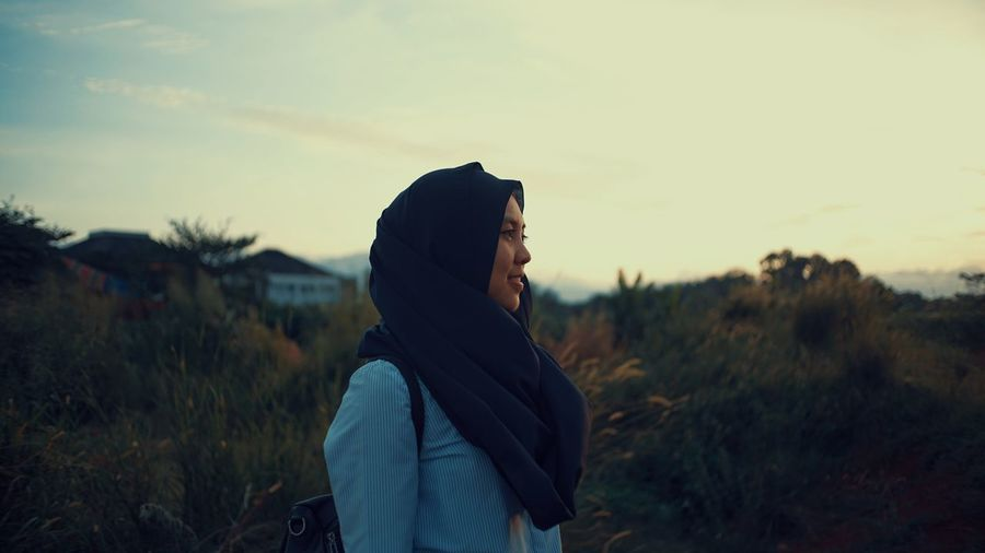 Side view of woman in headscarf standing against sky during sunset