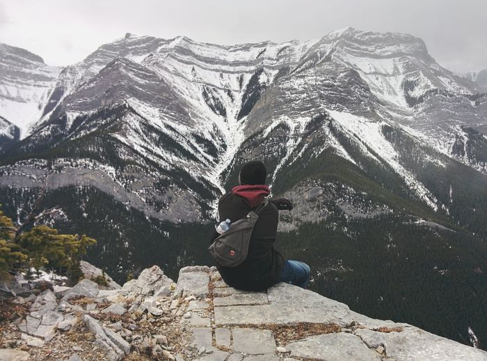 Rear View Of Man Sitting On Cliff Against Snowcapped Mountains