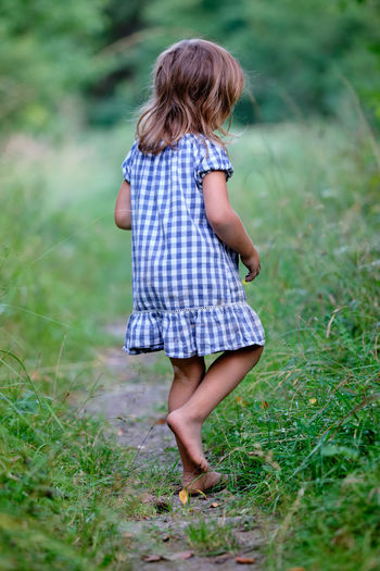 Rear view of girl standing on field