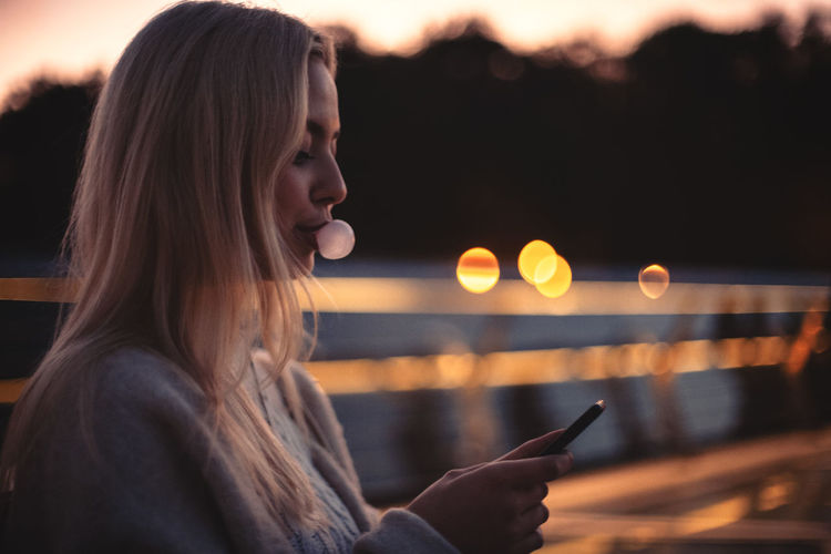 Portrait of young woman using mobile phone at night