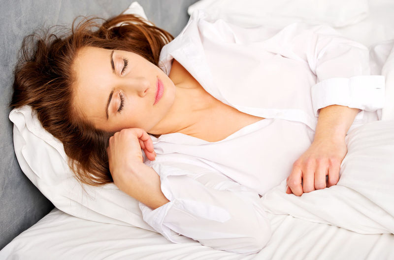 Young Woman Sleeping On Bed At Home