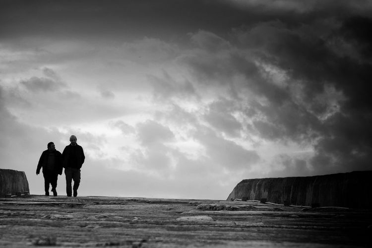 Rear view of silhouette man standing on sea shore against sky