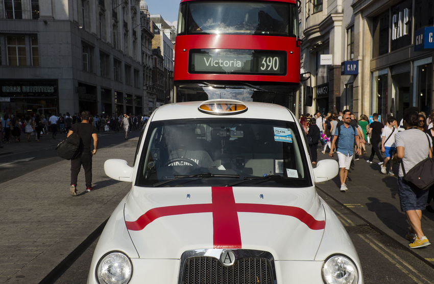 London taxi painted with the England national colours of the Saint George's Cross in Oxford on 9th of July 2018 in London, United Kingdom. (photo by Lorenzo Grifantini) Oxford Circus Patriotism Taxi Cab Car City City Street Double-decker Bus Group Of People Men Mode Of Transportation Motor Vehicle Outdoors Road Saint George's Cros Transportation Travel Destinations