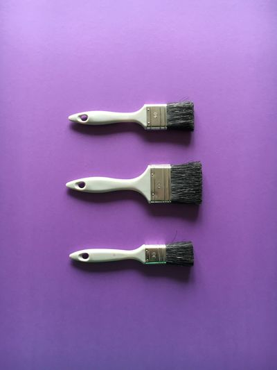 High Angle View Of Paintbrushes On Purple Background