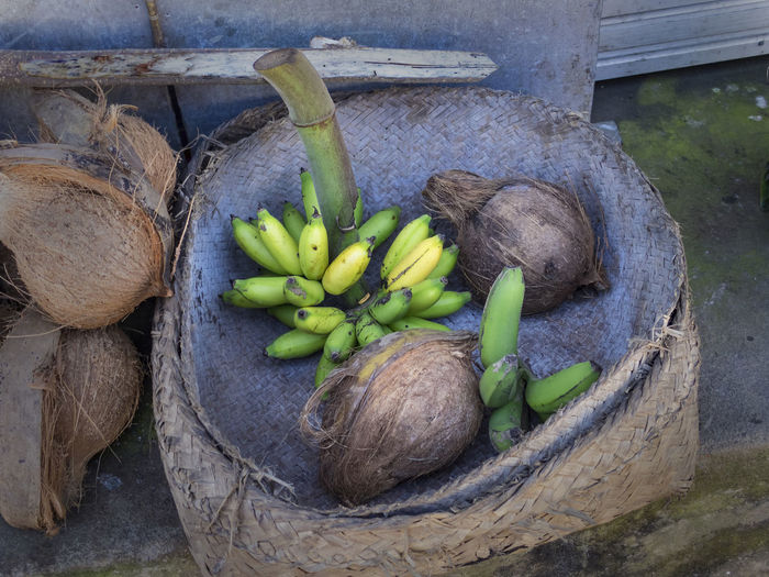 braided basket filled with bananas and coconuts, Yellow Purple Freshfruits Outfoor Food Food Markets Exotic Fruits Bali, Indonesia Asian Food Bananas Basket Coconuts Food Freshness Healthy Eating High Angle View No People Outdoors Rual Basket