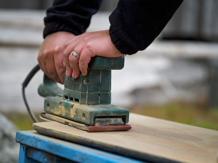Close up of a woman using a sander