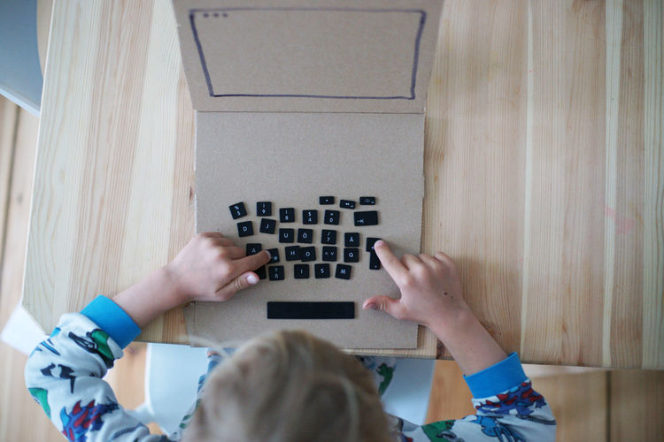 High Angle View Of Boy Playing With Computer Keys On Table