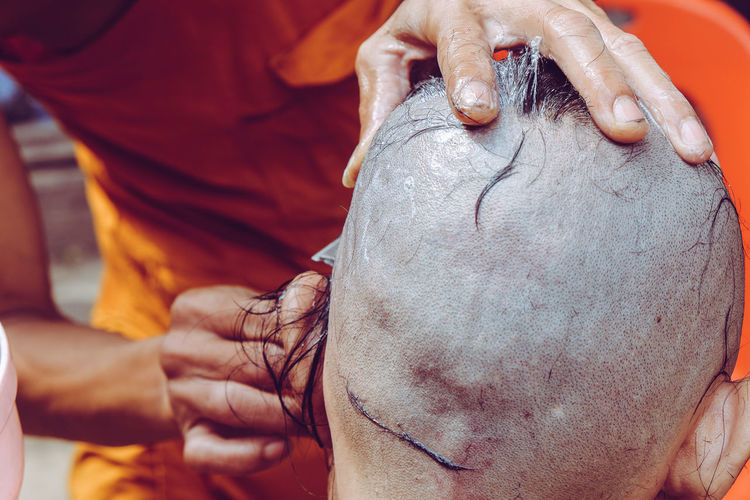 Midsection of monk cutting males hair