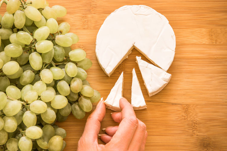 Agriculture Food And Drink Fresh Produce Freshness Freshnesss Tasting Wood Brie Camenbert Cheese Close-up Directly Above Food Fruits Grapes High Angle View Holding Human Body Part Human Hand Table Tastings Wine