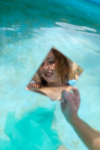 Young woman holding mirror with reflection in wading pool