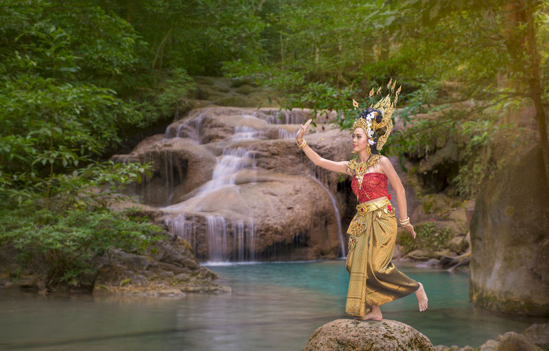 Beautiful young woman wearing crown and traditional clothing while dancing against waterfall in forest