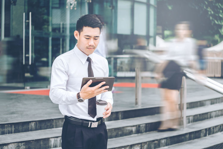 Businessman holding disposable cup while using digital tablet in city