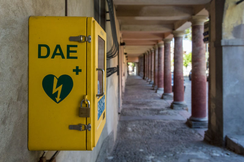 Meldola, Italy, close up of an automated external defibrillator (in italian abbreviation is DAE) place on public street Yellow Architecture Architectural Column Arcade Sign Corridor In A Row No People Focus On Foreground Communication Built Structure Day Building Direction Indoors  Text Diminishing Perspective The Way Forward Western Script
